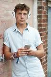 Teenage Boy Wearing Headphones And Listening To Music In Urban S. Teenage Boy Wearing Headphones And Listening To Music Stock Image