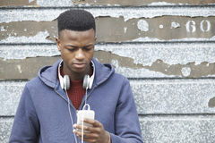 Teenage Boy Wearing Headphones And Listening To Music In Urban S. Teenager Wearing Headphones And Listening To Music In Urban Setting Stock Images