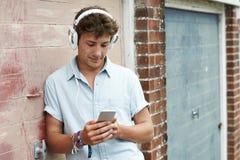 Teenage Boy Wearing Headphones And Listening To Music In Urban S. Teenage Boy Wears Headphones And Listens To Music In Urban Setting Stock Image