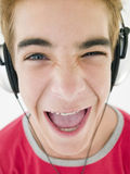 Teenage boy wearing headphones and smiling. At camera Royalty Free Stock Photography