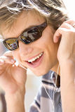 Teenage boy (16-18) wearing sunglasses and earphones, smiling, close-up Stock Images
