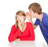 Teenage boy whispering in girlfriend ear Stock Photo