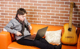 Teenage boy working on laptop. Concentration and composure. Royalty Free Stock Photos