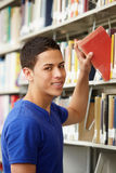 Teenage boy working in library Stock Photo