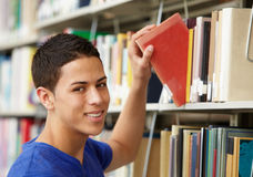Teenage boy working in library Royalty Free Stock Image