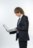 Teenage boy working in white laptop Stock Image