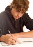 Teenage boy writing check. Or doing financial accounting Stock Photos