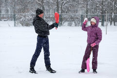 Teenage boy and young girl playing snowballs Royalty Free Stock Photo