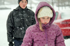 Teenage boy and young girl in snowing winter Stock Images