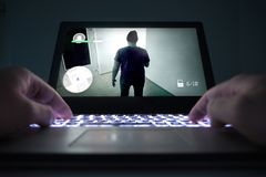 Teenage boy or young man playing action or crime video game. With laptop. Computer and online gaming concept. Low close up view to hands on keyboard Royalty Free Stock Image