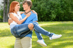 Teenage boyfriend carry girlfriend in his arms Royalty Free Stock Image