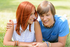Teenage boyfriend and girlfriend lying on grass Royalty Free Stock Images