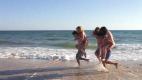 Teenage boys carrying girls along shore Royalty Free Stock Photos
