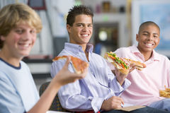 Teenage boys enjoying fast food lunches together Stock Images