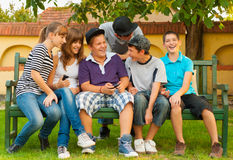 Teenage boys and girls having fun in the garden. While sitting on the bench stock photography