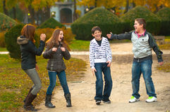 Teenage boys and girls having fun in the park. On beautiful autumn day stock photography