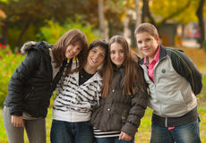 Teenage boys and girls having fun in the park. On beautiful autumn day stock photo