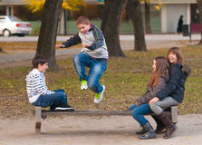Teenage boys and girls having fun in the park. On beautiful autumn day royalty free stock photography