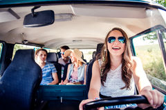Teenage boys and girls inside an old campervan, roadtrip. Teenage boys and girls inside an old campervan on a roadtrip, girl driving, sunny summer day royalty free stock photography