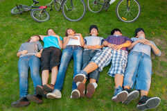 Teenage boys and girls lying in the grass Royalty Free Stock Photography