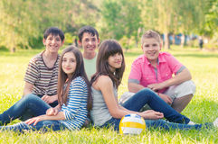 Teenage boys and girls resting in grass after playing soccer royalty free stock photo