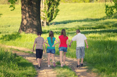 Teenage boys and girls walking in nature on sunny spring day royalty free stock images