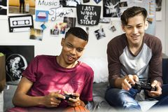 Teenage boys hanging out in a bedroom playing video games together Stock Image