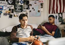 Teenage boys hanging out in a bedroom. Playing a video game and using a smartphone Stock Photography