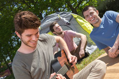 Teenage boys near tent playing guitar Royalty Free Stock Photography