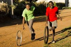 Teenage Boys Playing with Wheel Stock Photo