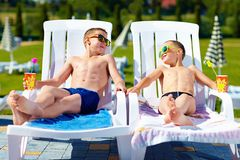Teenage boys relaxing on sunbeds in waterpark Stock Photography