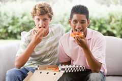 Teenage Boys Sitting On Couch Eating Pizza Stock Photos