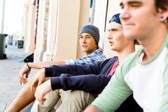 Teenage boys sitting at the street Royalty Free Stock Image
