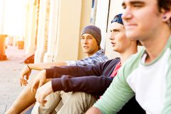 Teenage boys sitting at the street Stock Photography