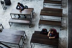 Teenage boys sitting by themselves in an empty canteen Royalty Free Stock Image