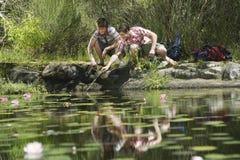 Teenage Boys Squatting By Lake Stock Photo