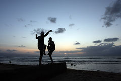 Teenage Boys at sunset. Teenage boys, balancing on a stone wall and play fighting at sunset stock image