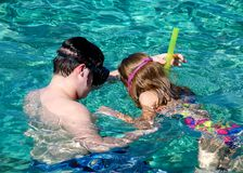 Teenage Brother Helping Sister Learn to Snorkel. Teenage Brother helps his sister learn how to snorkel in the beautiful waters off of Cozumel, Mexico Royalty Free Stock Images