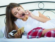 Teenage brunette enjoying chocolate bar in bed Royalty Free Stock Images