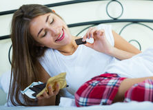 Teenage brunette enjoying chocolate bar in bed Royalty Free Stock Image