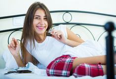 Teenage brunette enjoying chocolate bar in bed Royalty Free Stock Photography