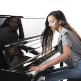 Teenage brunette girl and black upright piano in studio Royalty Free Stock Photo