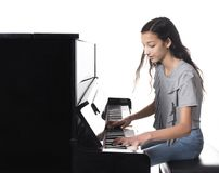 Teenage brunette girl and black upright piano in studio Stock Image