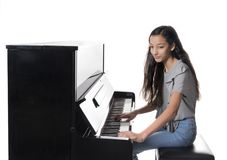 Teenage brunette girl and black upright piano in studio Stock Photos