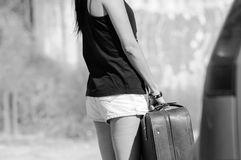 Teenage brunette woman holding a large leather suitcase Stock Photography