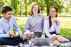 Teenage Children Enjoying Picnic. Portrait of three happy students relaxing during picnic on green lawn outdoors, using laptop and laughing Stock Photo