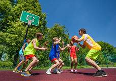 Teenage children playing basketball game together Stock Photos
