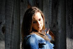 Teenage Country Girl. Young teenage girl posing beside a wooden wall Royalty Free Stock Image