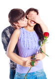 Teenage couple. Happy beautiful  teenage couple, a boy giving a rose to his girlfriend and kissing her Stock Photography