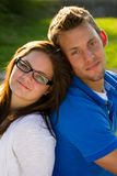 Teenage Couple. A teenage boy and a teenage girl with glasses leaning back to back Royalty Free Stock Photos